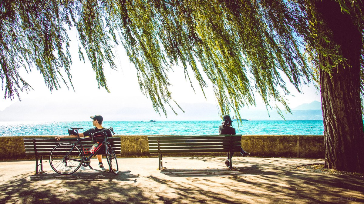 Street portrait of a man and a woman sitting on benches near the lake Leman