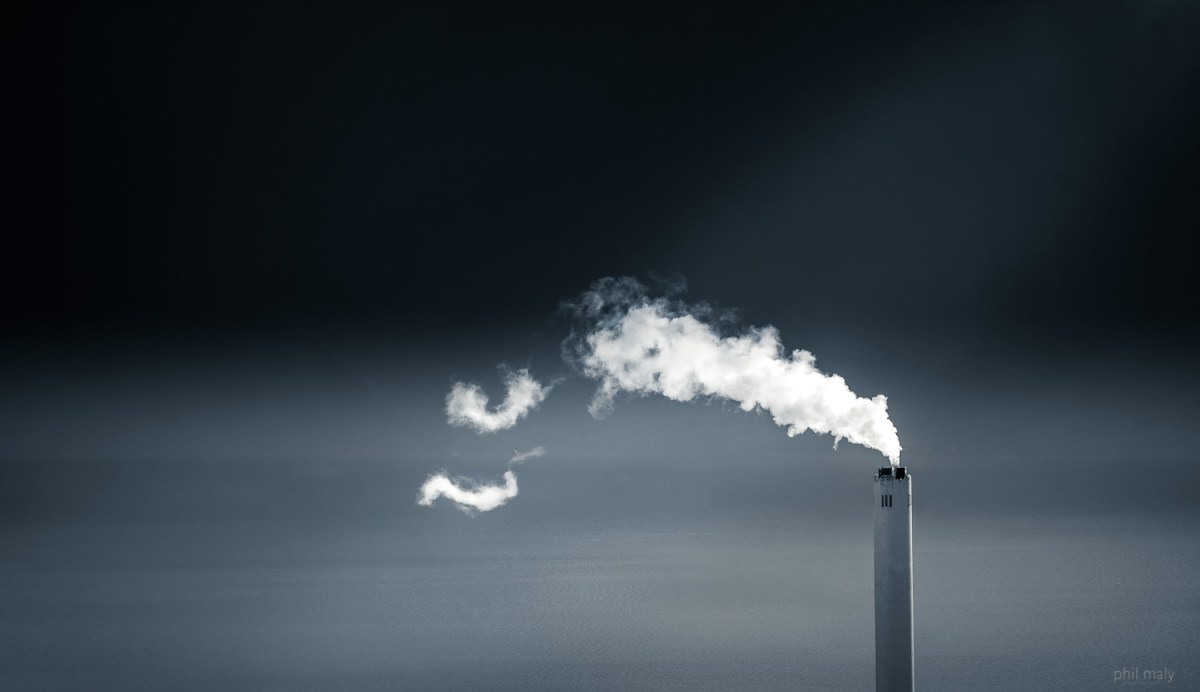 Minimal shot of a factory chimney with its smoke