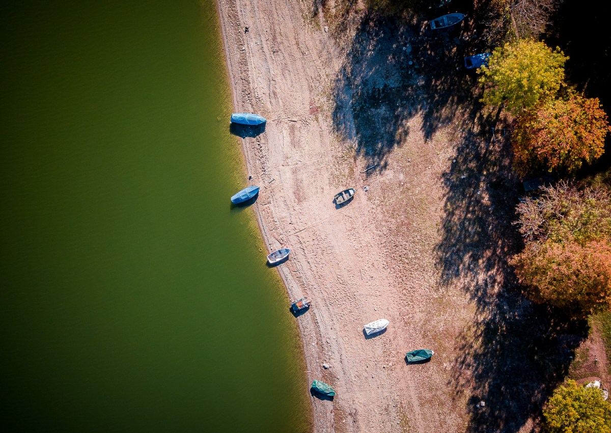 Top down drone shot of small boats on the dry bank of the lake of Bret