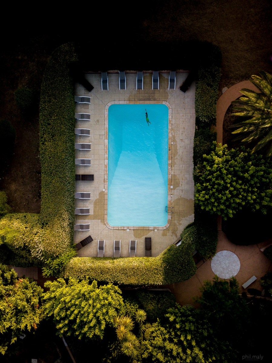 Top down drone shot of a swimming pool with a single boy swimming