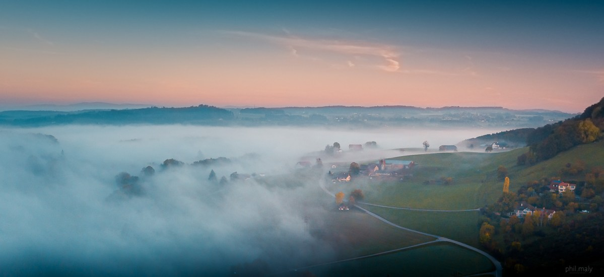 Flying the drone above the mist slowly covering a little village at sunrise