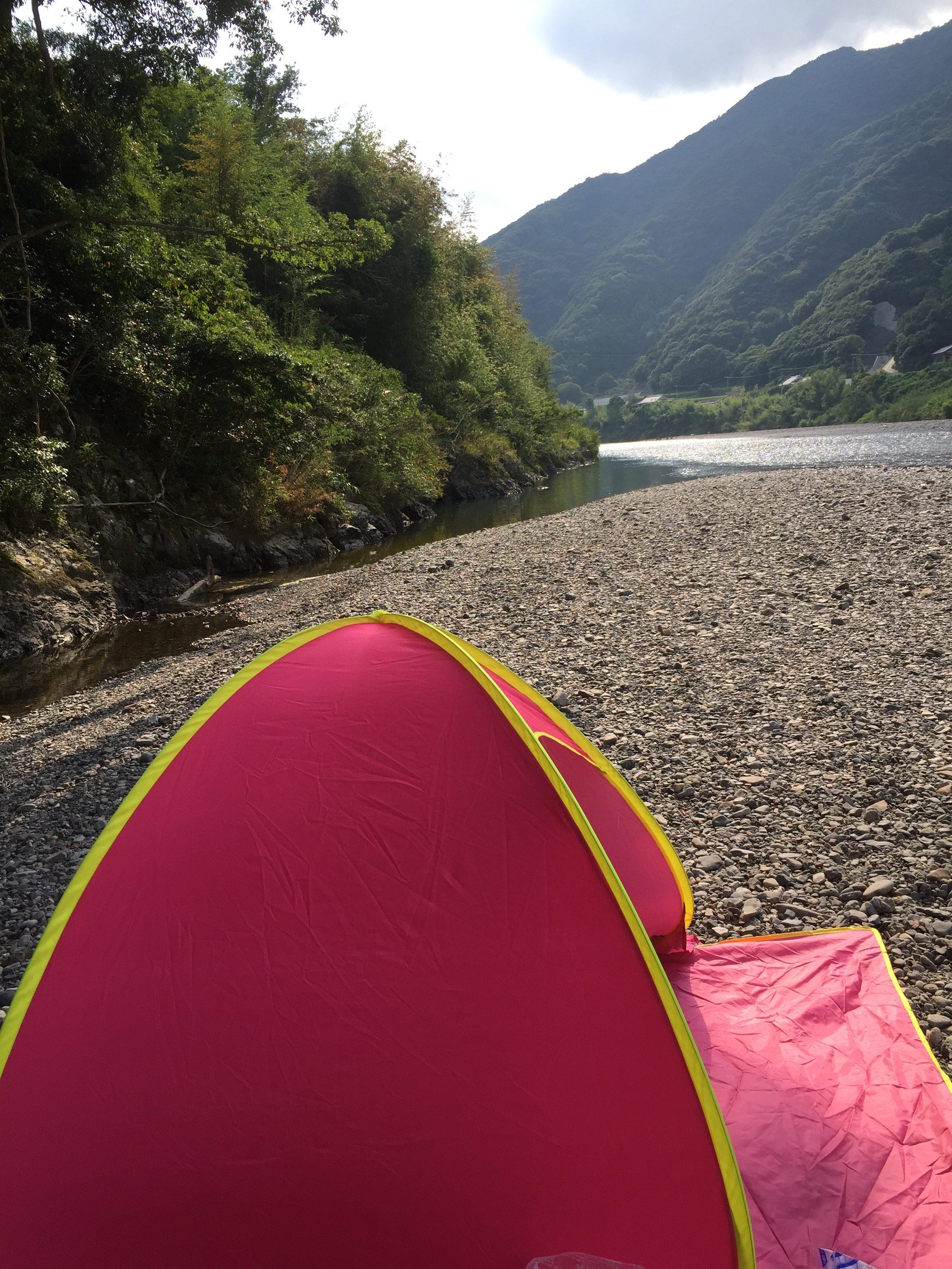 河原でポップアップテントを広げた様子