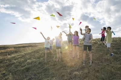 子供達が草原に向かって紙飛行機を飛ばす