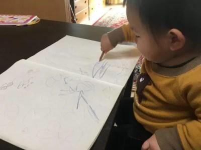 色鉛筆でぐちゃぐちゃとお絵かきをする1歳児