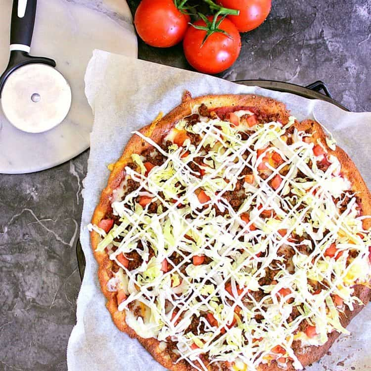 Taco Pizza using a fathead pizza crust and loaded with taco seasoned beef, diced tomatoes, lettuce, sour cream and green onion.
