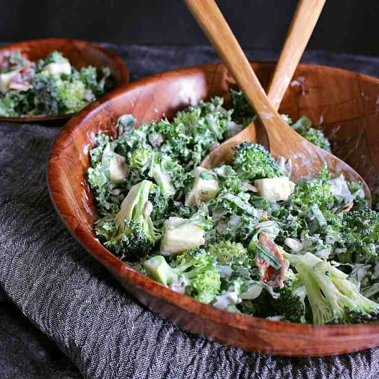 Serving bowl with low carb broccoli salad with serving spoons. Side salad behind.