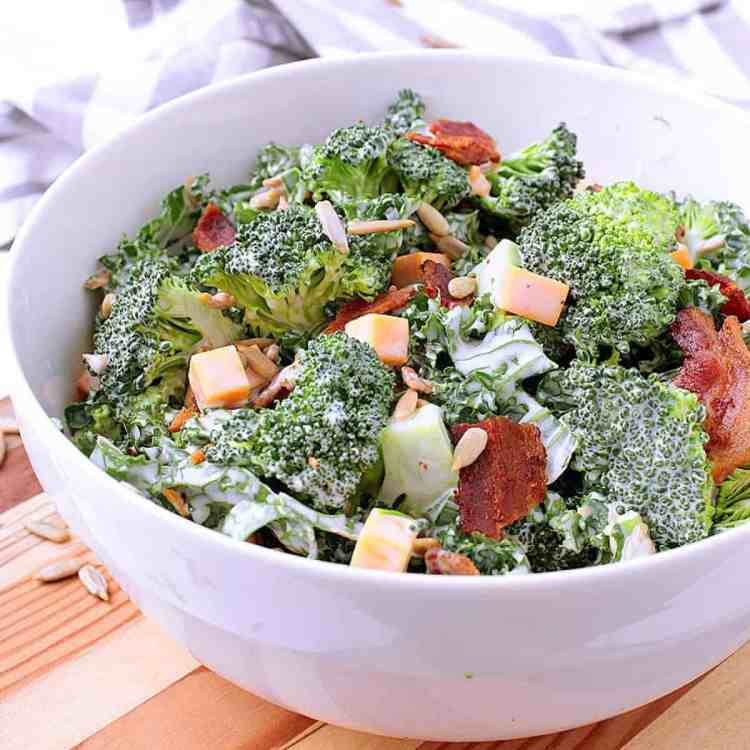 Serving bowl filled with low carb broccoli salad, next to serving spoons and a small bowl.