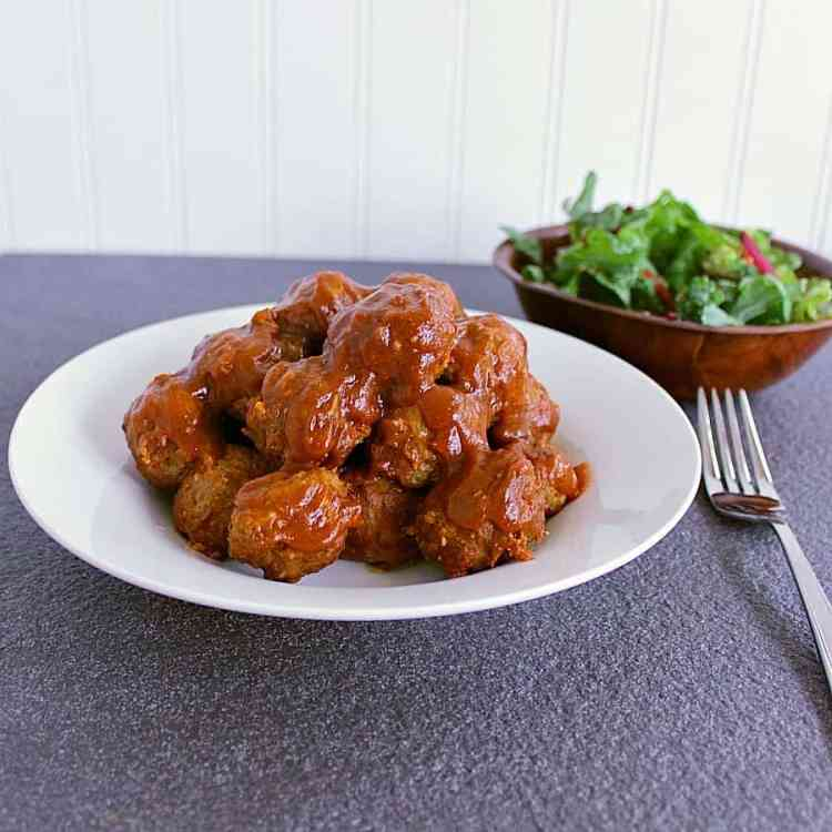 Bowl of low carb meatballs with a salad behind.