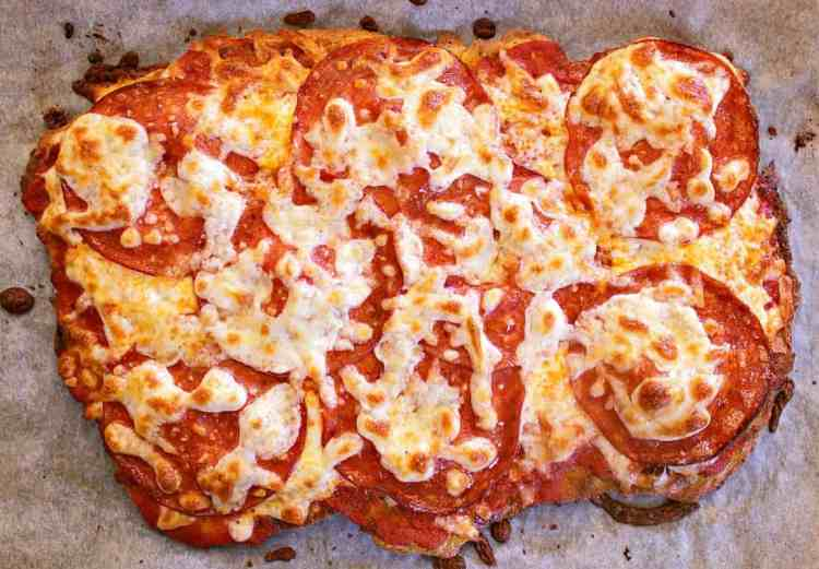 Freshly baked pizza, ready to be sliced into sections.