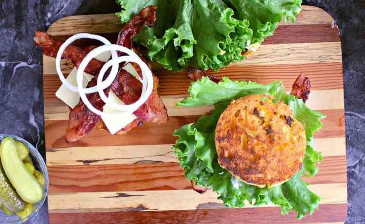 One burger fully made, the other burger has the turkey burger patty, aged cheddar, bacon and onion.