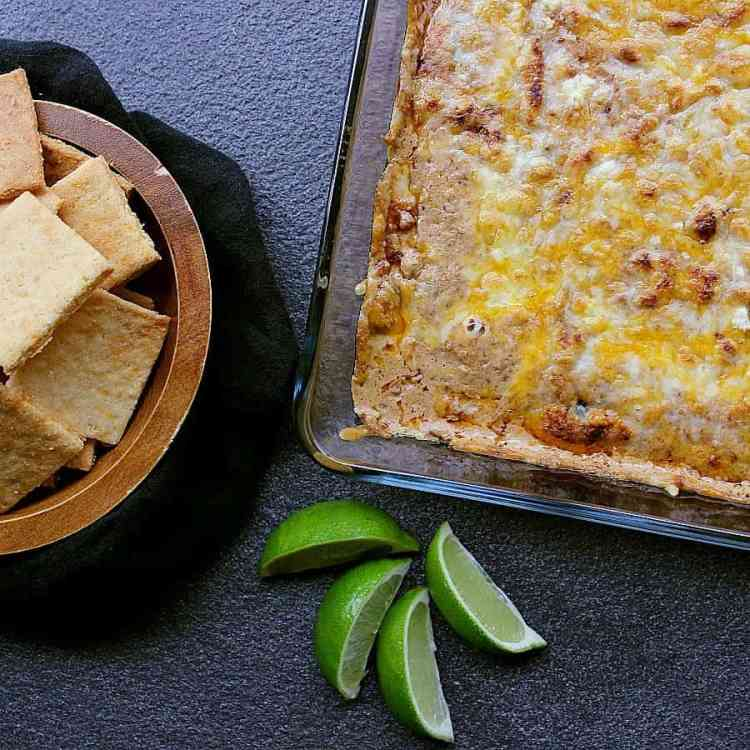 hot bean and cheese dip next to a bowl of low carb cheese crackers.