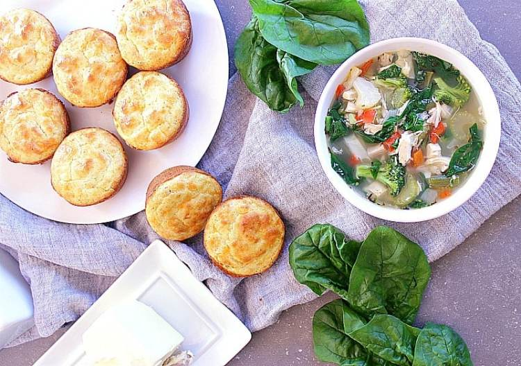 Bowl of fully loaded low carb chicken soup besides some low carb biscuits.