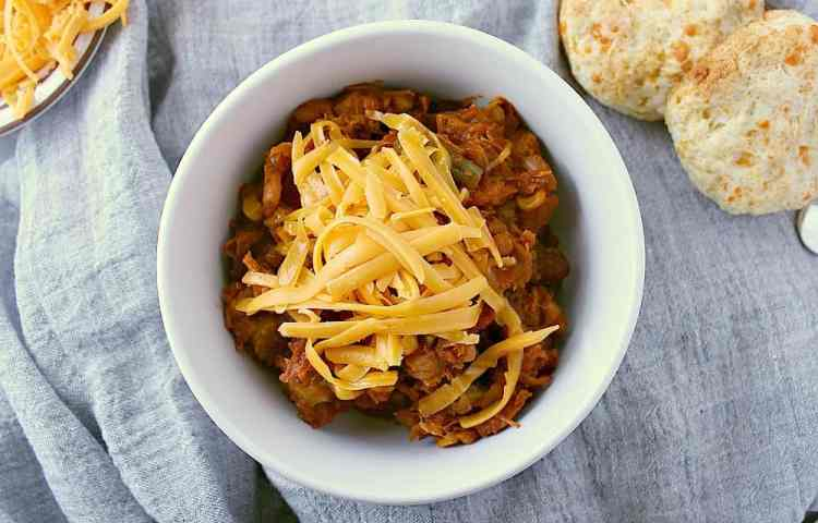 Single bowl of leftover turkey chili with grated cheddar cheese on top.
