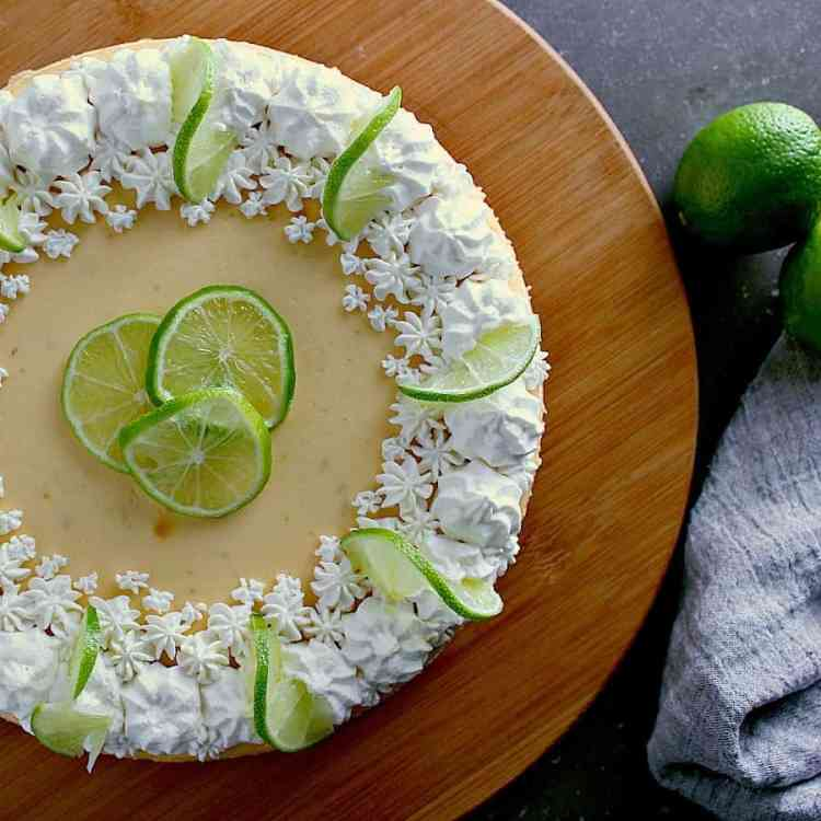 Top of the cheesecake, displaying freshly whipped cream with lime slices.