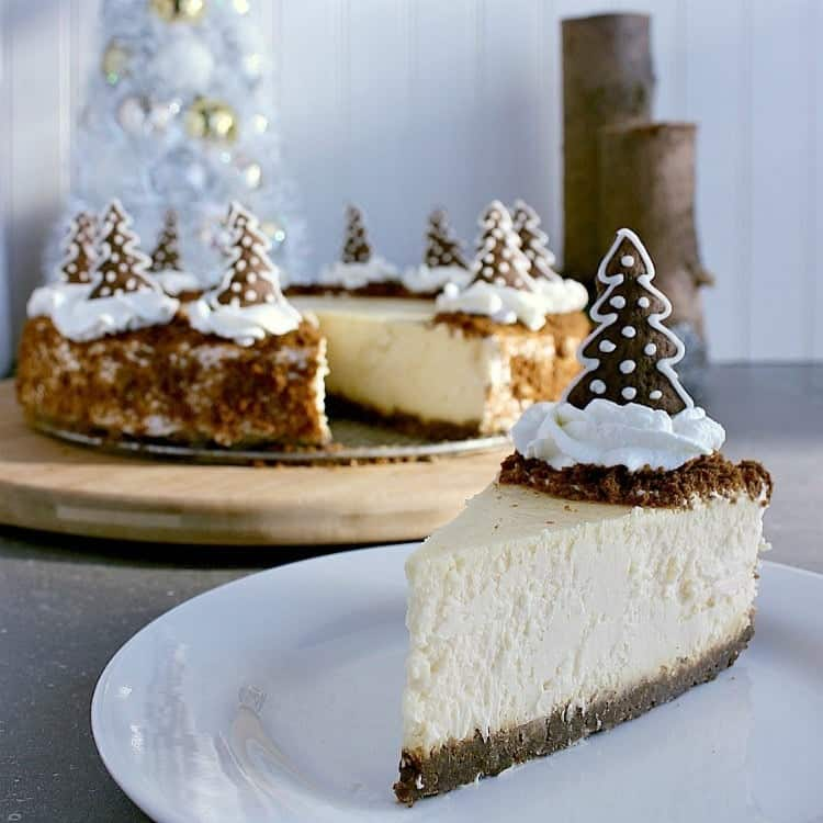 Slice of gingerbread crust cheesecake with a gingerbread tree on top, the whole gingerbread cake is in the background.