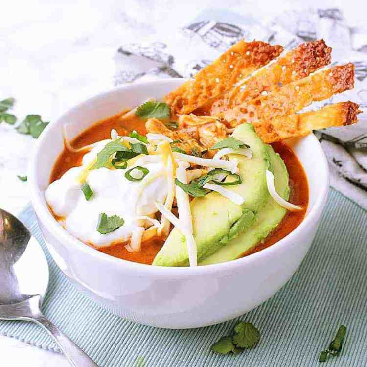 Bowl of instant pot low carb chicken taco soup, garnished with cheese crisps.