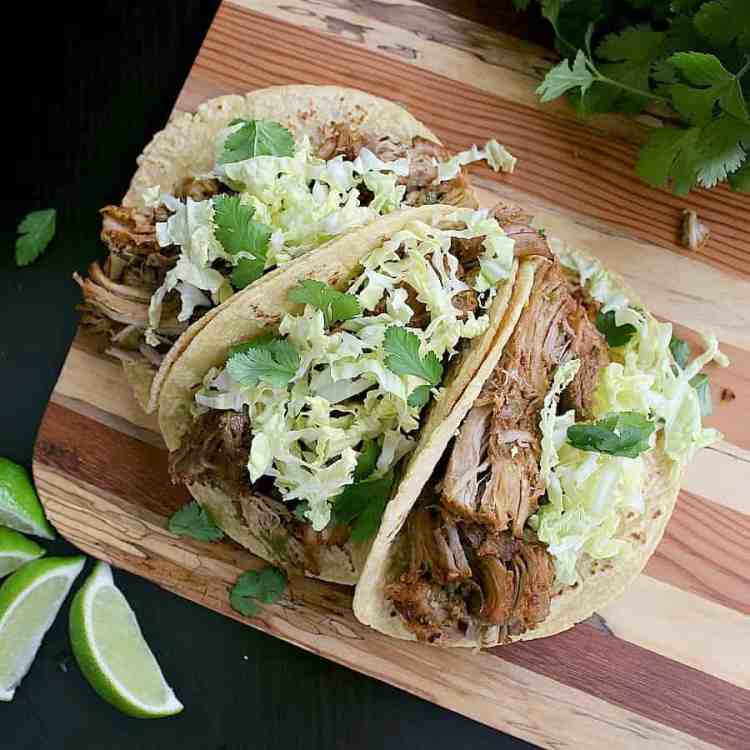 Three corn tortillas loaded with Instant Pot Carnitas, shredded cabbage and fresh cilantro.