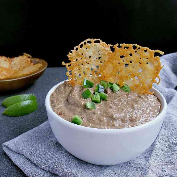 Bowl of Instant Pot Low Carb Refried Beans with cheese crisps.