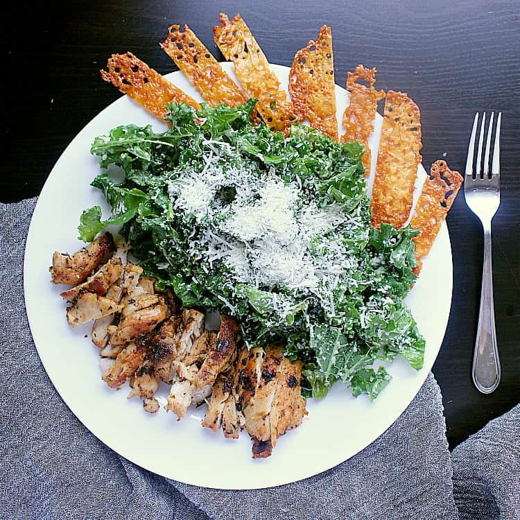 Caesar salad with pan fried chicken thighs, garnished with cheese crisps.