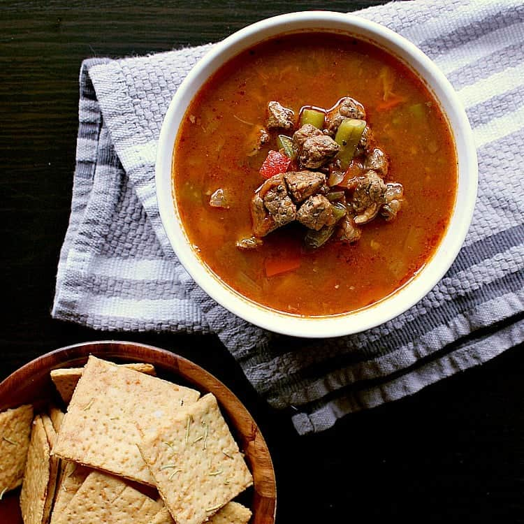 Bowl of low carb vegetable beef soup next to a bowl of low carb crackers.