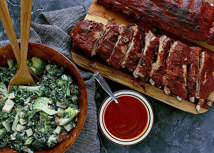Two racks of ribs, one sliced into sections, next to a big bowl of broccoli salad and extra low carb barbecue sauce.