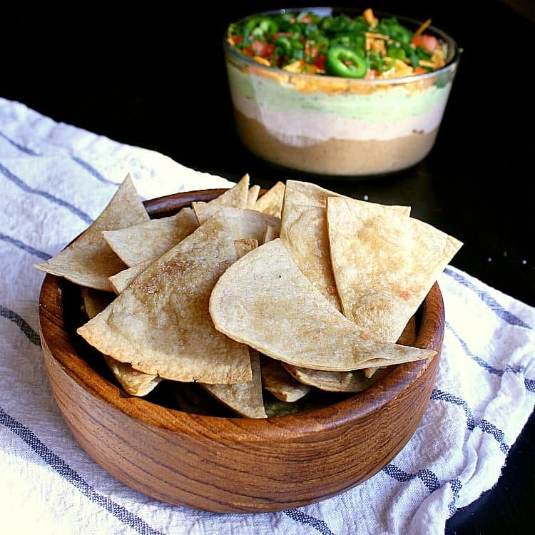 A bowl of low carb baked tortillas chips with a low carb 7 layer dip in the background.