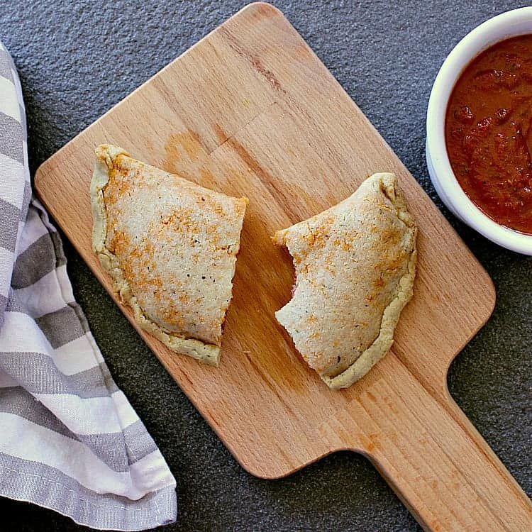 Two keto calzone halves on a wooden cutting board with one bite taken out of one half.