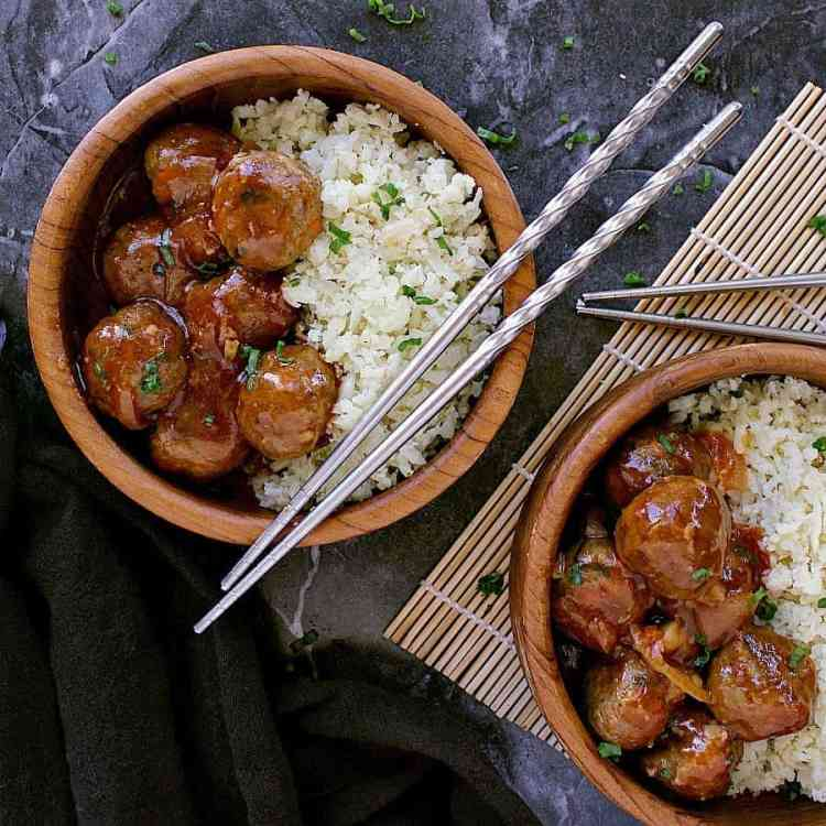 Two bowls of keto sweet and sour meatballs with cauliflower rice on the side. Garnished with chopped green onion and chopsticks.
