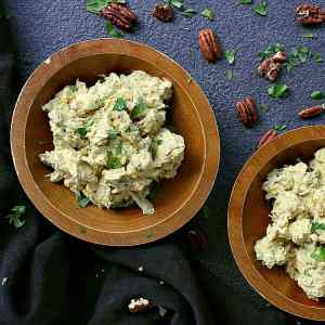 Two bowls of low carb curry chicken salad in wooden bowls. A garnish of pecans and cilantro is spread around the bowls.