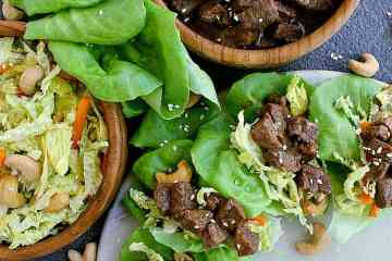 butter lettuce leaves filled with korean beef and asian slaw, next to a bowl of korean beef and another bowl of low carb asian slaw.