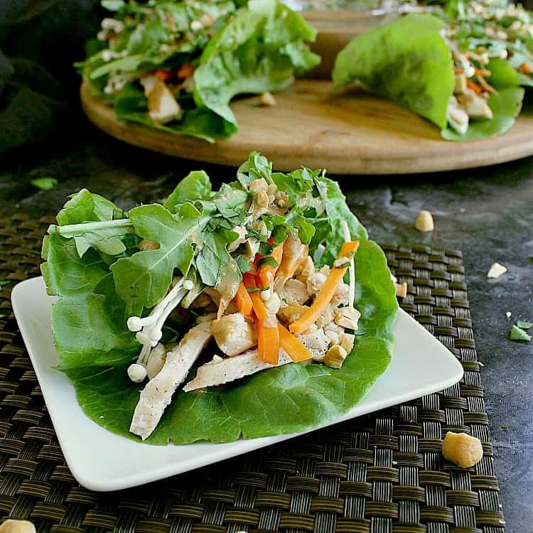 Single keto chicken lettuce wrap on a small plate with the platter of wraps behind.
