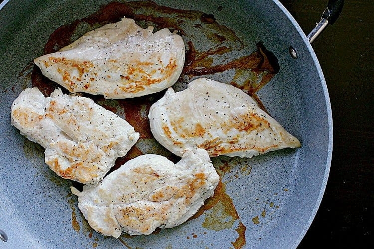 Fried chicken breasts in a skillet, ready to be cooled.