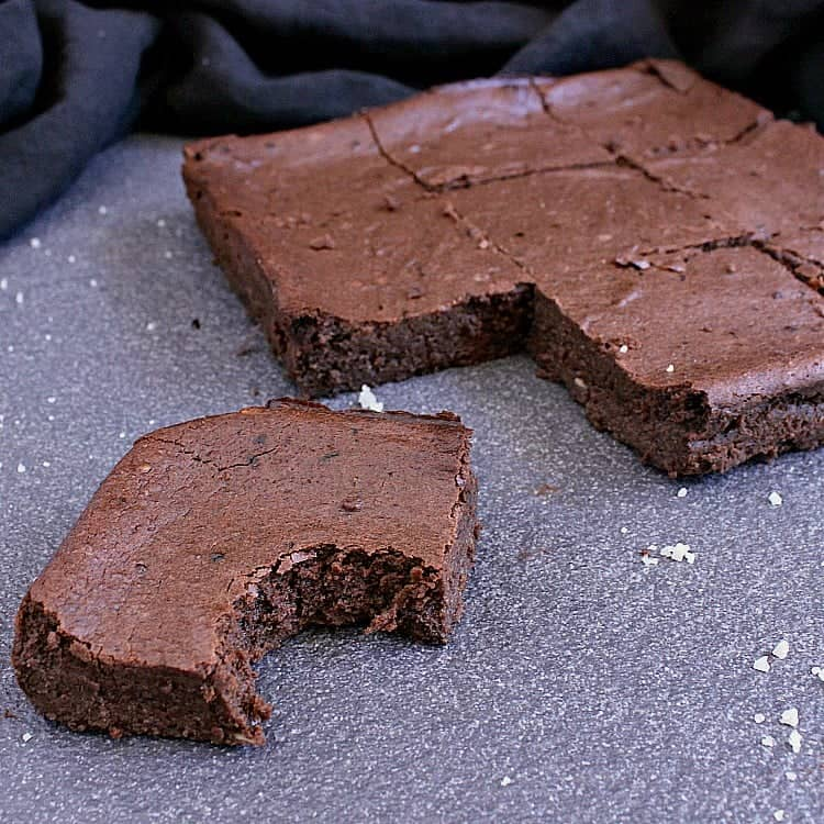 9 keto chocolate brownies, one with a bite taken out.