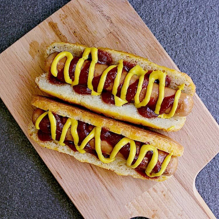 Two keto hot dog buns with hot dogs, ketchup and mustard.