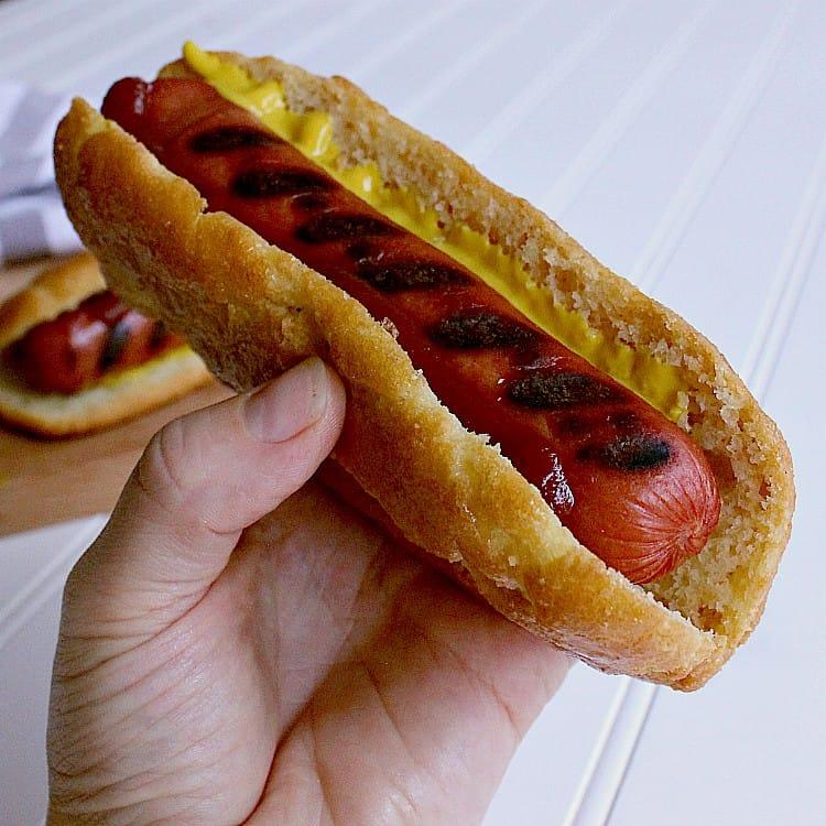 Hot dog in a keto hot dog bun with ketchup and mustard.