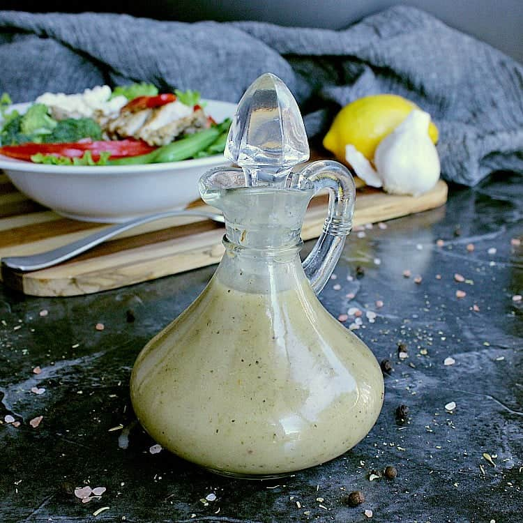 Glass dressing jar with keto Italian dressing. A fresh green salad is in the background with a lemon and some garlic.