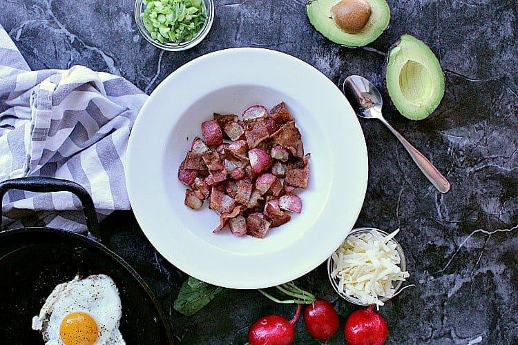 Bowl of roasted radishes and chopped bacon.