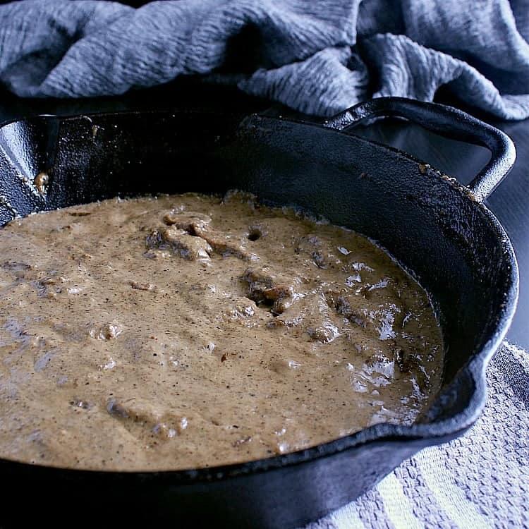 Cast iron skillet full of keto mushroom sauce.