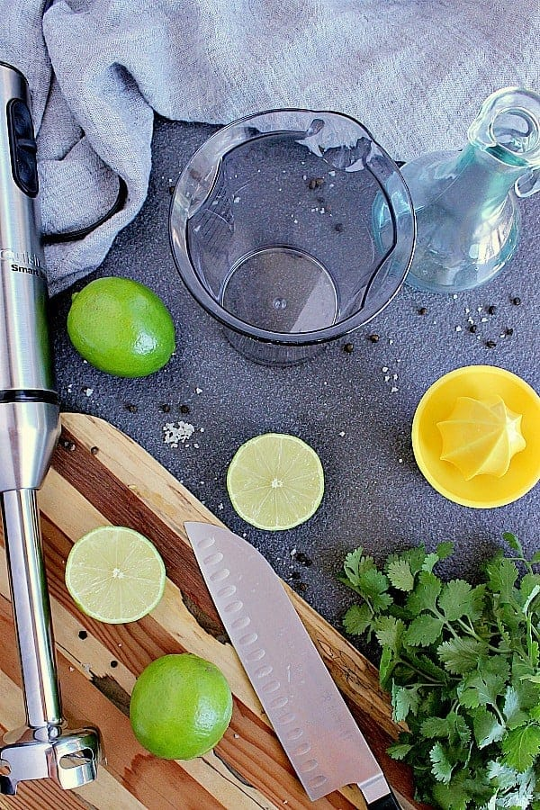 Immersion blender next to some limes, fresh cilantro, knife and lime juicer.