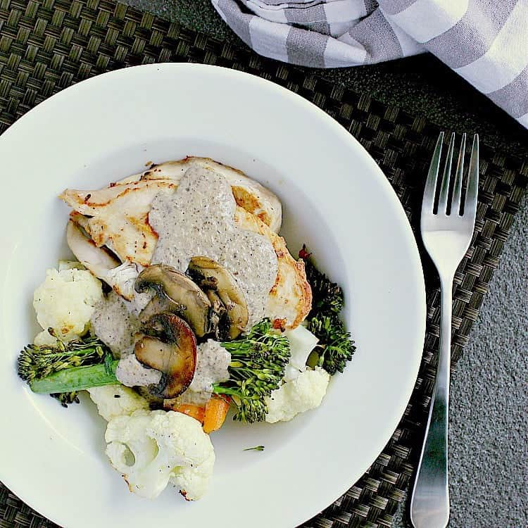 Seared chicken breast with roasted vegetables and covered in keto mushroom sauce.