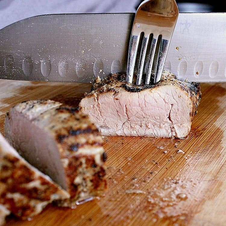 Pork tenderloin slices on a cutting board, the rest of the tenderloin behind about to be sliced up.