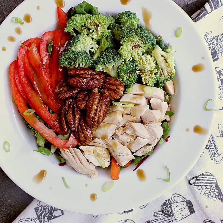 Salad bowl with tossed salad, sliced red pepper, broccoli, chicken breast and a balsamic dressing. The salad is garnished with sugar free candied pecans.