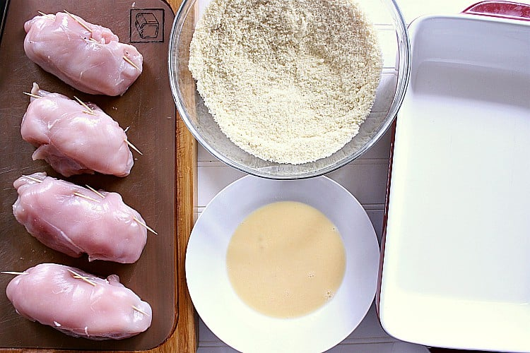 workstation prepped with the prepared chicken breasts, egg wash, almond flour mixture and baking dish.