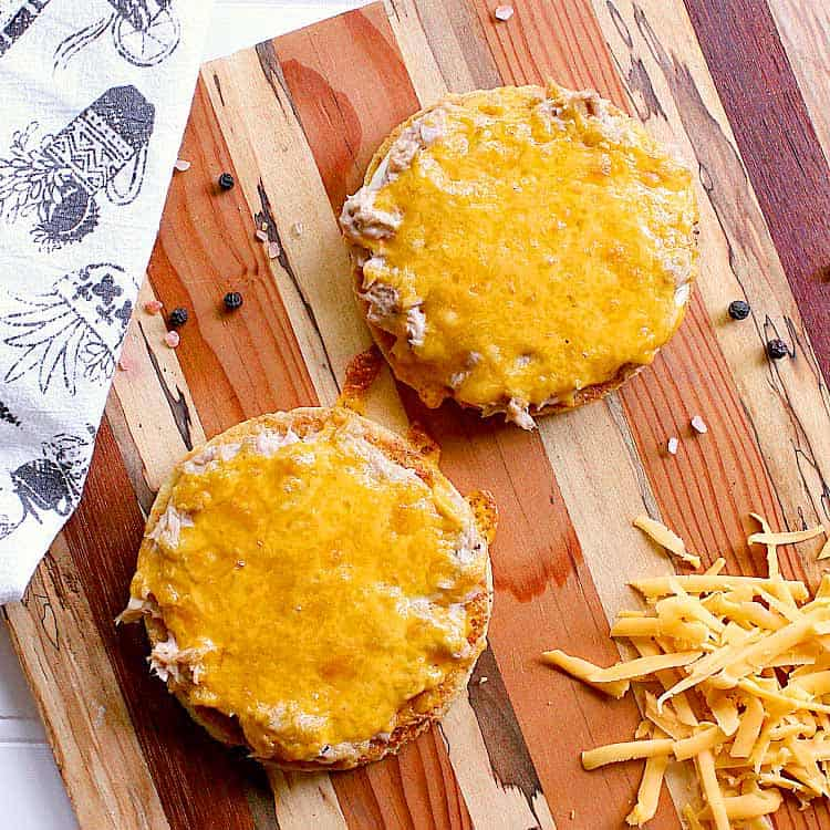 Two keto tuna melts freshly baked, laying on a wooden cutting board.