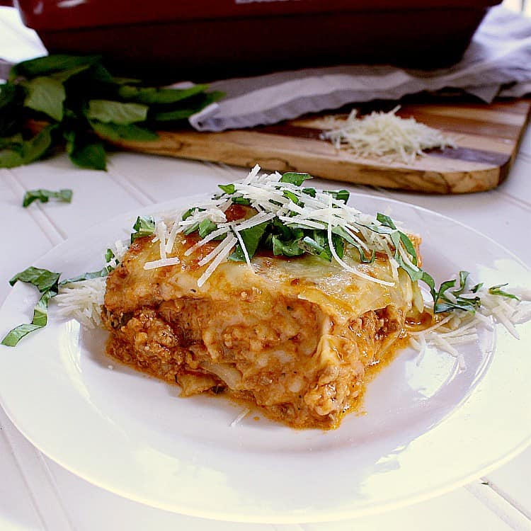 One slice of low carb cabbage lasagna, topped with parmesan and basil.