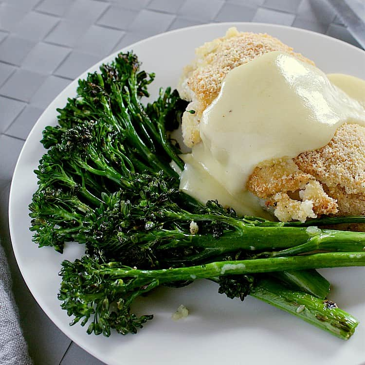 Plate with chicken cordon bleu, garlic sautéed broccolini and topped with keto cheese sauce.