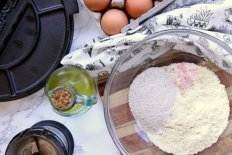Bowl of almond flour, psyllium husk and salt next to olive oil, eggs and a tortilla pres.