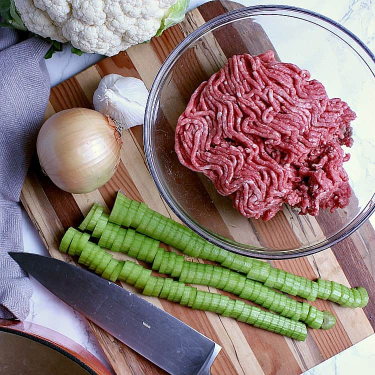 Cutting board with chopped celery, a small onion, head of cauliflower and garlic, and a bowl of ground beef.