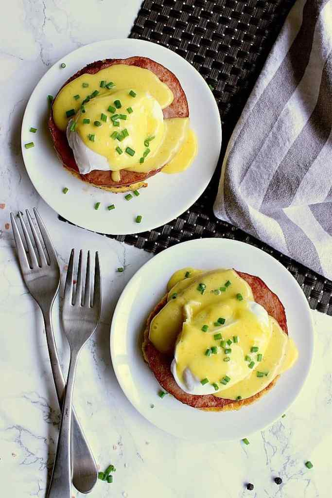 Two plates with eggs benedict, covered in keto hollandaise sauce.