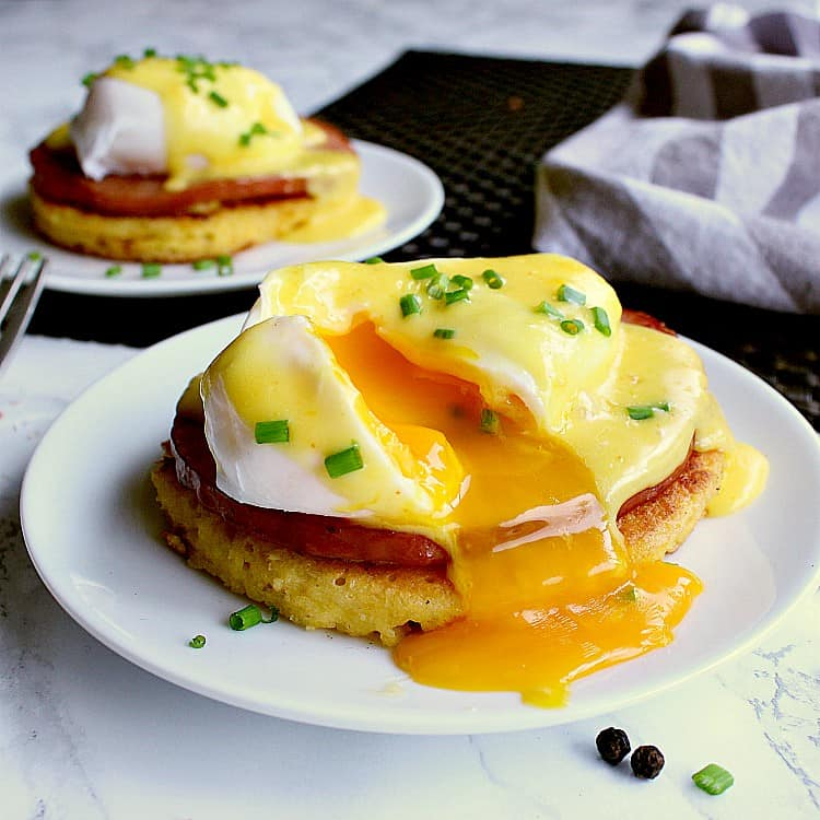 Two plates each with a keto eggs benedict and garnished with chives. One of the eggs is cracked to expose the perfectly poached soft yolk.